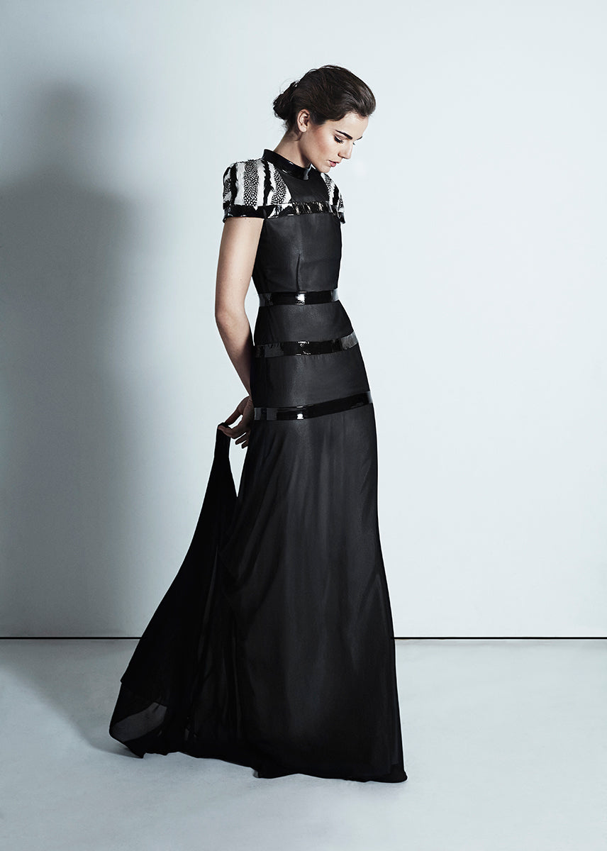 Black gown with sleeves embellished in feathers and leather details around the middle
