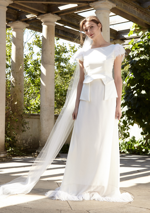 The white bridal gown is a two-piece dress detailed with feathers at the sleeves and skirt