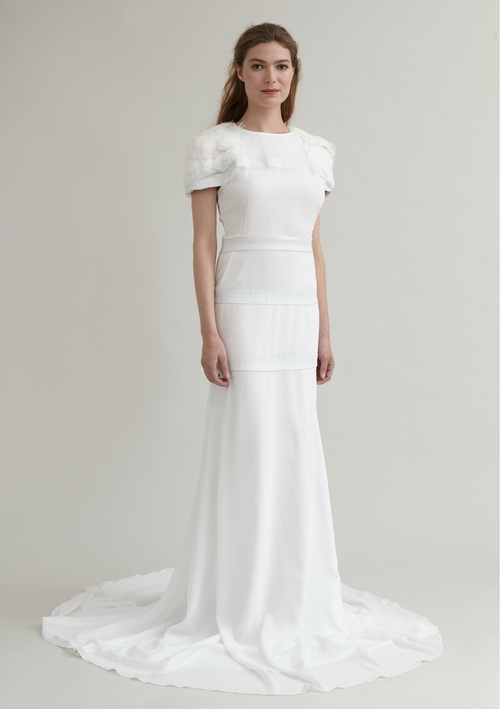 Flowing chiffon bridal gown with leather bands and feathers on the sleeves