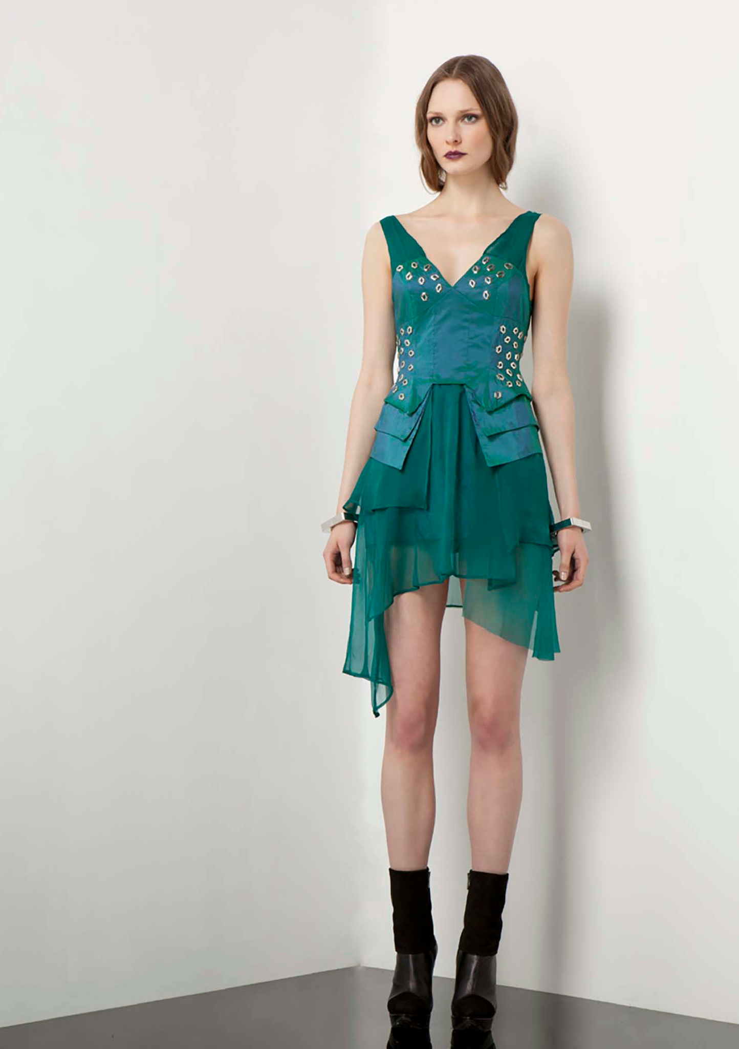 Asymmetric, green cocktail dress with a studded detail on the chest and waist