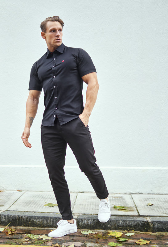 bodybuilder in stretch shirt and black chinos