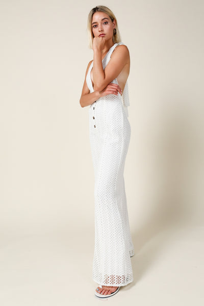 Sleeveless, halter neck jumpsuit with front button detail.