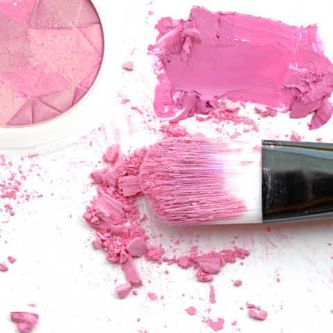 Makeup brush with blush product on it