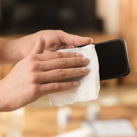 Person sanitizing their phone