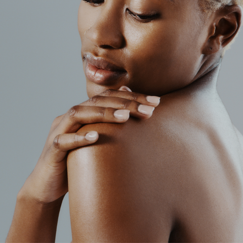 Woman rubbing skincare product on her shoulder