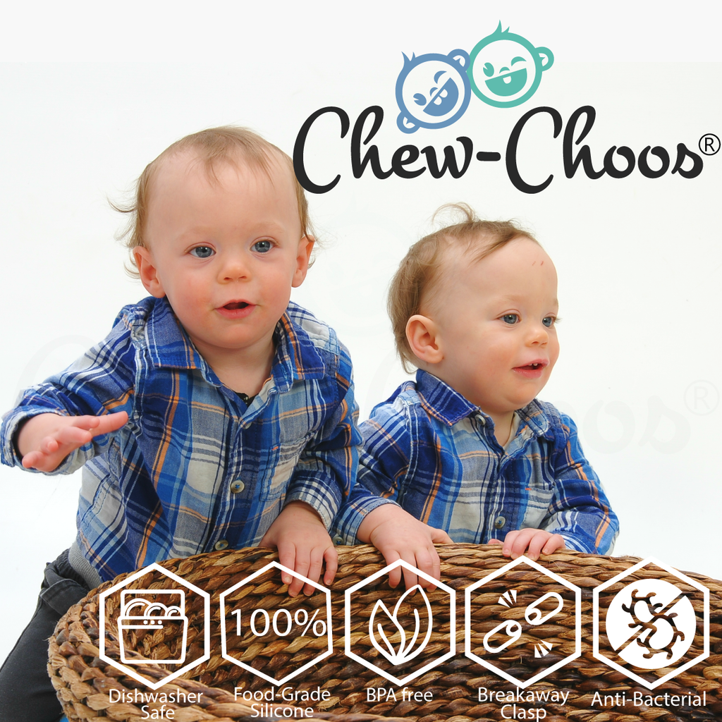 Twin baby boys playing with basket full of safety and handling information for Chew-Choos