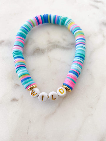 """Wild"" in Gold Letters on Aqua Rainbow Color Pop Bracelet"