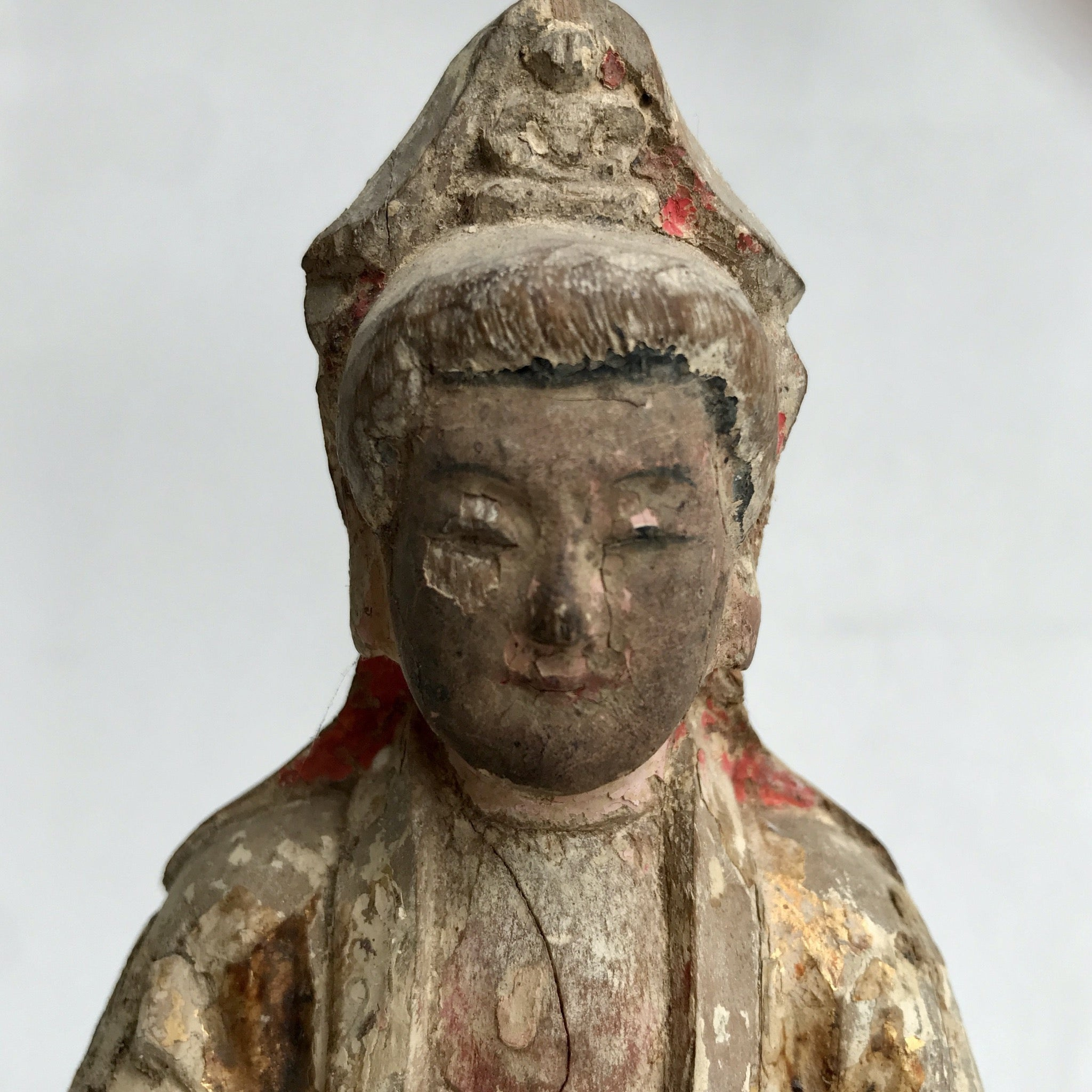 Close up of face of Quan Yin. Buddha in her headdress and flecks of red and gold paint remaining. She has a quiet expression.