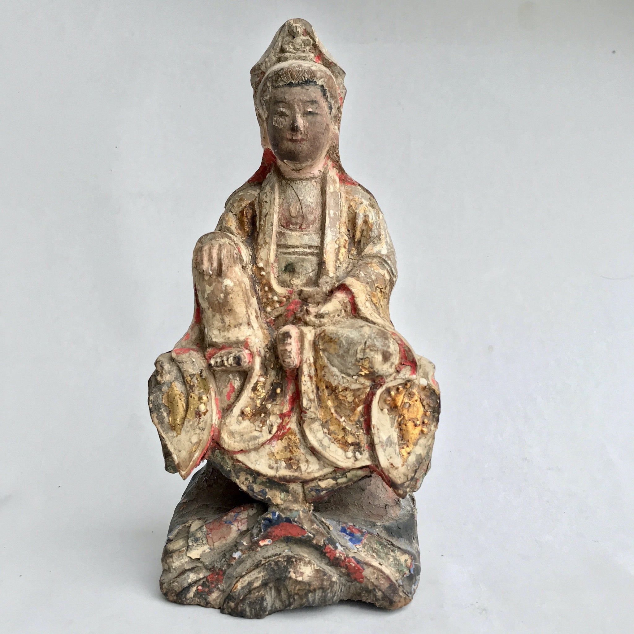 A very old small Quan Yin statue. 8 1/2 inches 20cm She is seated in Royal Ease. One foot up with a hand rising on it ad her other hand in her lap. Most of her paint is gone but you can see layers of red and blue with bits gold details.