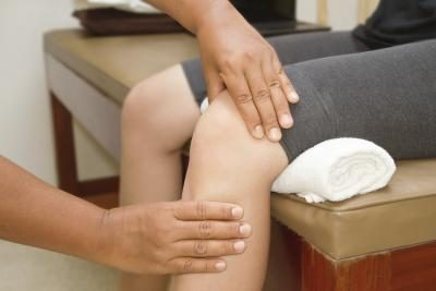 A physical therapist examines a patient's knee