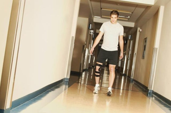 A man wearing a knee brace walks down an hospital corridor