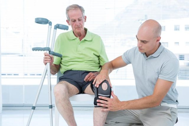 A doctor adjusts a knee immobilizer on a patient.