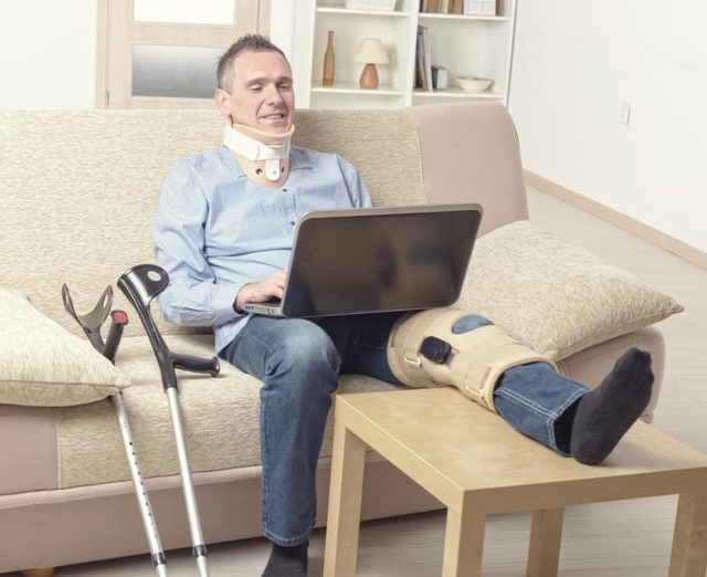 A man sits on the couch working on his laptop with a knee brace on post knee surgery.