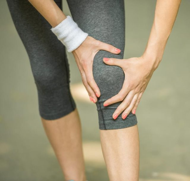 A woman hold her knee during a workout.