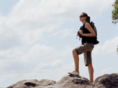 A woman is hiking outside.