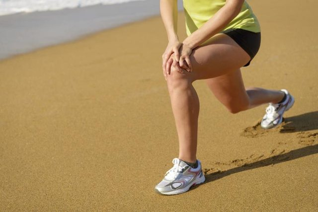 A woman is lunging on the sand.