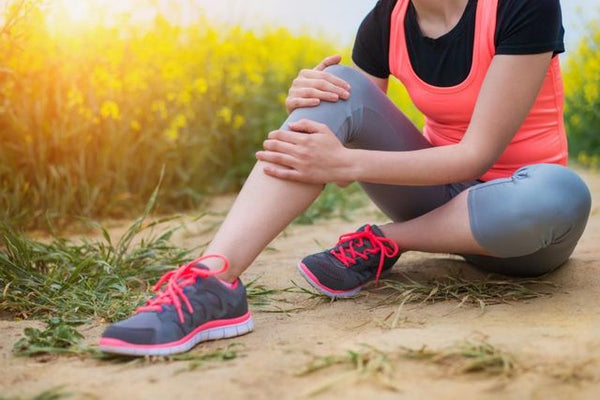 A young female runner with a sore knee