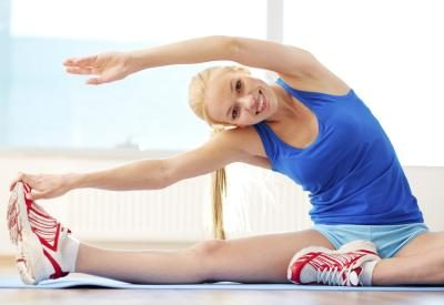 A young woman is doing stretches in the gym.