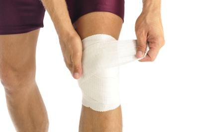 Man wrapping knee in bandage.