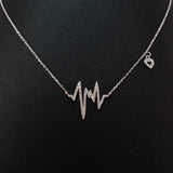 925 STERLING SILVER NECKLACE WITH EKG HEARTBEAT PENDANT SET IN SPARKLING CRYSTALS.
