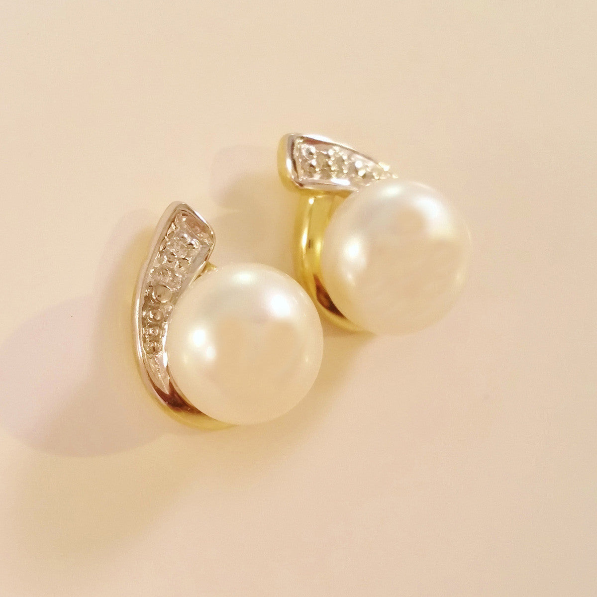 9K SOLID GOLD 7.00MM FRESHWATER PEARL AND DIAMOND EARRINGS.