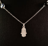 925 STERLING SILVER NECKLACE WITH TURKISH EVIL EYE CHARM AND HAMSA HAND PENDANT SET IN SPARKLING CRYSTALS.