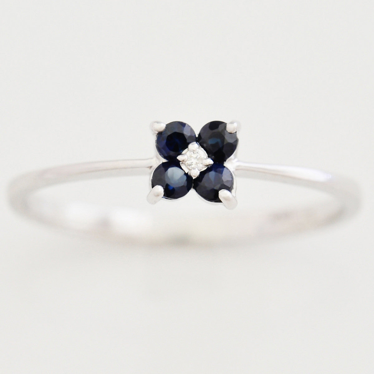 9K SOLID WHITE GOLD 0.20CT SAPPHIRE FLORAL CLUSTER RING WITH CENTRE DIAMOND.