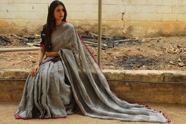 Grey with zari border linen Saree with contrast pink tassels. NF-LL4-C5-The Chalk Boutique