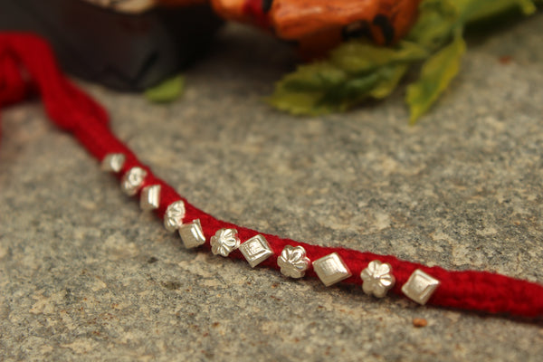 Red Hand Knotted rakhi (Wristband) in silver . VA-AG18-8-RED