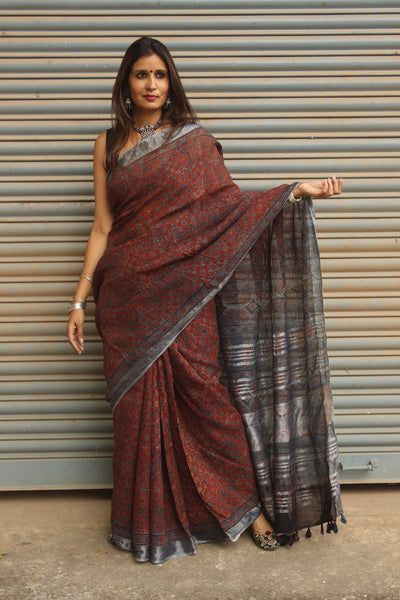 Handloom Ajrakh linen saree with zari border and tasseled pallu.