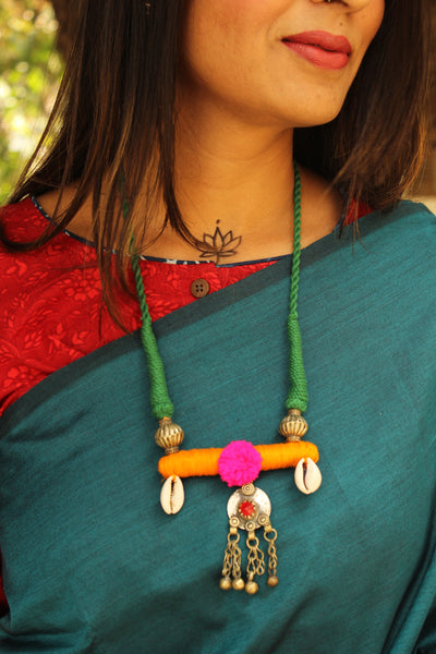Adjustable dori necklace with shell beads, coin and pompom. CC-CH2B-C2