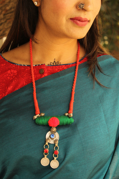 Adjustable dori necklace with coin and pompom. CC-CH2C-C2