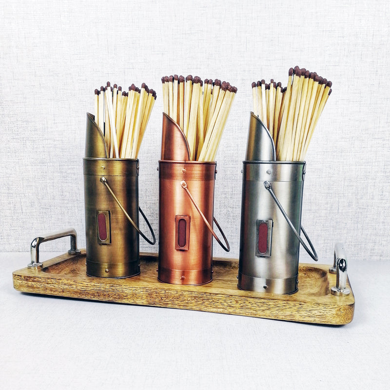 Matchstick holders bronze pewter copper on wooden tray against grey background