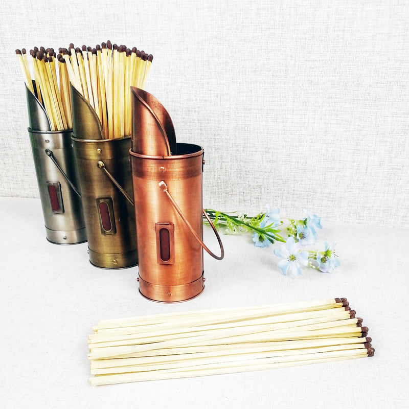 Matchstick holders bronze pewter copper with matches and flowers blue against grey background