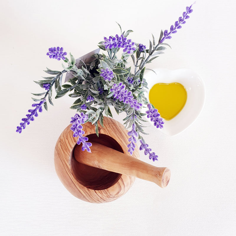 Top-dwon view of olive wood pestle and mortar with oil an dlavendar