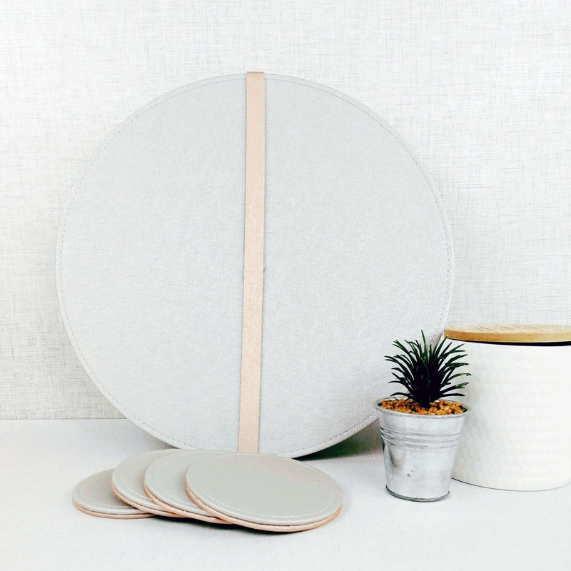 Reversible Placemat and Coaster Set nex tto small plant and white jar on white table