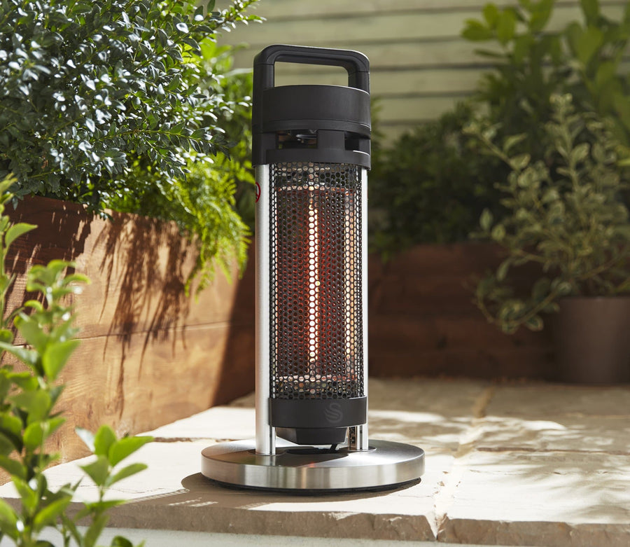 A portable stand patio heater in an outdoor sunny area. Greenery in the background.