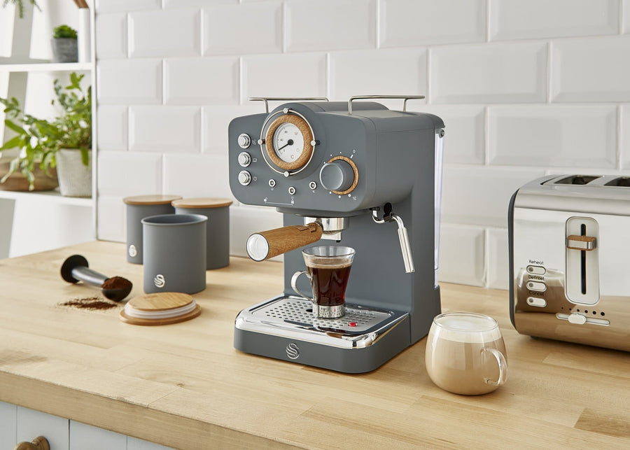 A kitchen surface with white tiles and a wood desktop. A grey nordic style coffee machine between some grey canisters and toaster. Two cups of coffee shown in front of the machine.