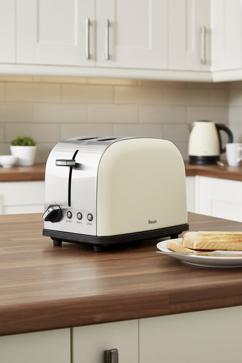 Cream Swan Camden 2-Slice Toaster on wooden countertop next to a plate of toast