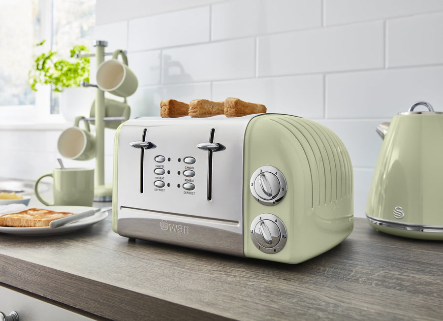 A kitchen counter with light green Retro toaster with toast popping up. Next to a light green kettle, mugs and mug tree. White tiling behind the products.