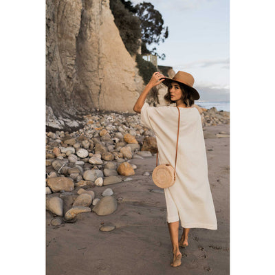 pokoloko-womens-bali-bag-tan-classic-dress-natural-editorial-walking-on-beach-looking-over-shoulder-wide-brim-hat