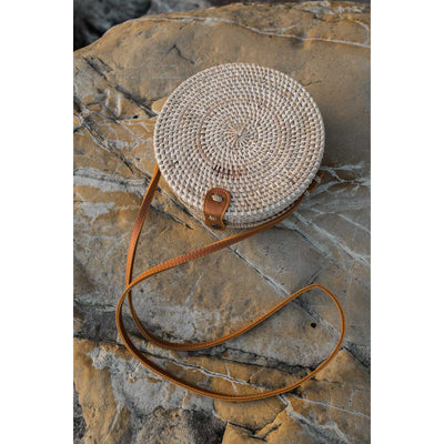 pokoloko-womens-bali-bag-tan-editorial-outside-on-rocks-woven-rattan-circular-bag-vegan-leather-straps-and-buckle