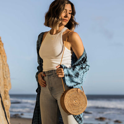 pokoloko-womens-bali-bag-caramel-circular-woven-rattan-vegan-leather-straps-and-buckle-blue-tye-dye-duster-kimono-jeans-and-white-tank-top-editorial-beach-sky
