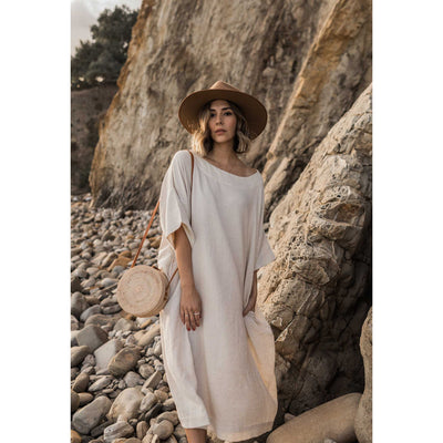pokoloko-womens-classic-dress-natural-forward-facing-standing-beach-rocks-bali-bag-tan