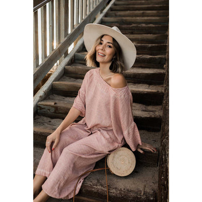 pokoloko-classic-dress-rose-off-shoulder-sitting-on-stairs-outside-bali-bag-tan-wide-brim-hat-smiling-sunshine