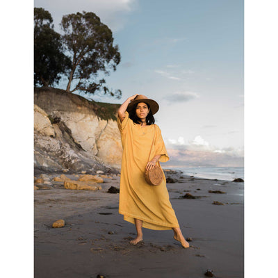 pokoloko-womens-classic-dress-mustard-standing-on-beach-leg-extended-hand-on-wide-brim-hat-bali-bag-caramel-sunshine