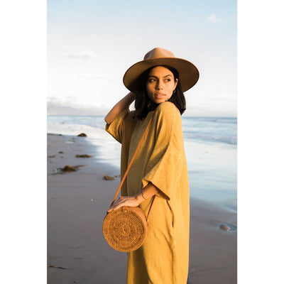 pokoloko-womens-classic-dress-mustard-side-profile-looking-over-shoulder-bali-bag-caramel-beach-wide-brim-hat