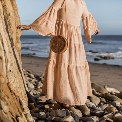 pokoloko-womens-long-dress-simply-taupe-editorial-cropped-showing-back-of-dress-bell-sleeves-bali-bag-caramel-standing-on-beach