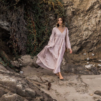 pokoloko-womens-long-dress-simply-taupe-editorial-walking-on-beach-near-rocks-v-neck-bell-sleeves-a-line-bali-bag-caramel