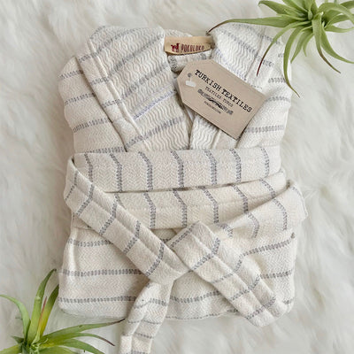 pokoloko-striped-bamboo-bath-robe-mist-color-folded-flat-lay-next-to-air-plants